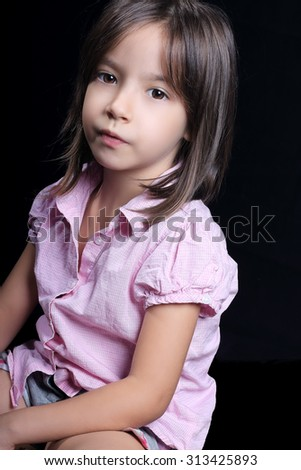 Portrait of cute little girl looking at camera, on dark background
