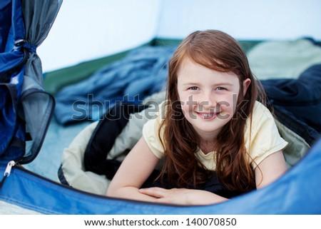 Portrait of cute little girl lying in tent - stock photo