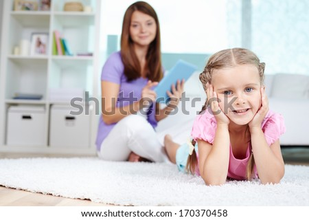 Portrait of cute little girl lying on the floor with her mother on background