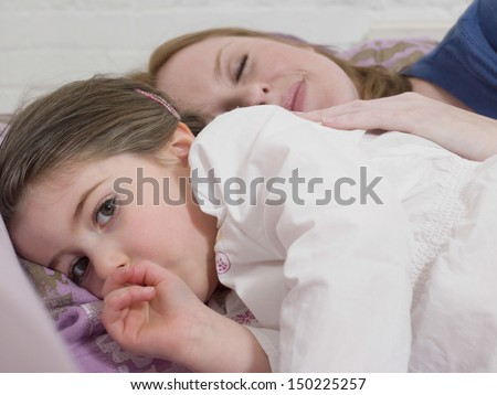 Portrait of cute little girl lying with mother in bed