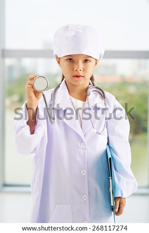 Portrait of cute little girl playing doctor with stethoscope