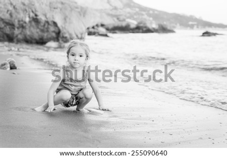 portrait of cute little girl playing on the beach at sunset ( black and white ) - stock photo