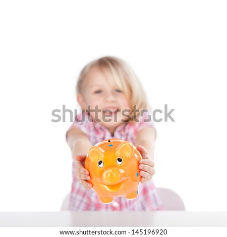 Portrait of cute little girl showing orange piggybank isolated over white background