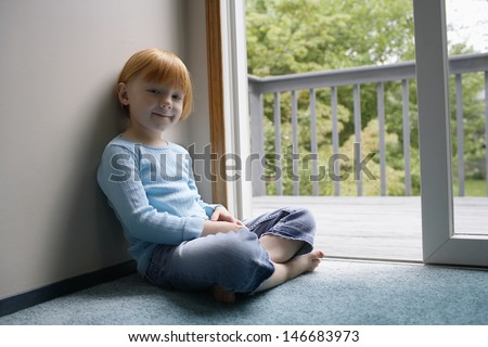 Portrait of cute little girl sitting by balcony at home