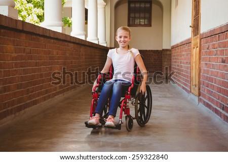 Portrait of cute little girl sitting in wheelchair in school corridor - stock photo