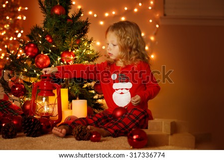 Portrait of cute little girl sitting under Christmas illuminated tree and holding lantern with pajamas at home, horizontal with copy space - stock photo