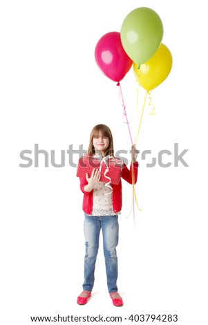 Portrait of cute little girl standing at isolated white background while holding in her hands balloons and a gift box.