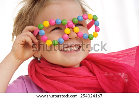 Portrait of cute little girl wearing funny glasses, decorated with colorful candies. Four years old child smiling, having fun.