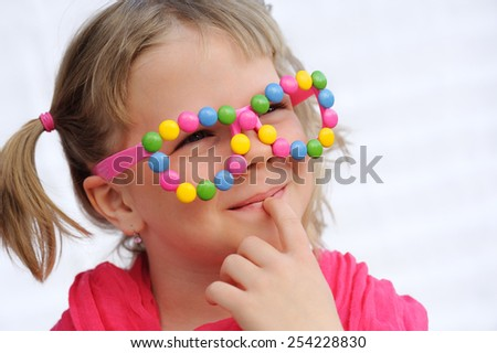 Portrait of cute little girl wearing funny glasses, decorated with colorful sweets, candies. Seven years old child having fun, smiling