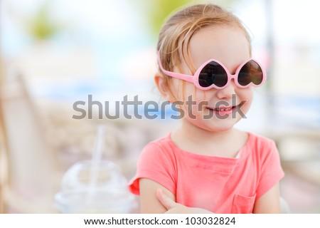 Portrait of cute little girl wearing sun glasses upside down - stock photo