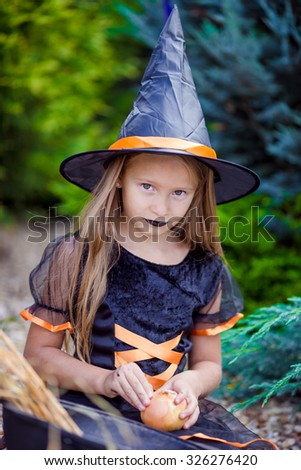 Portrait of cute little girl wearing witch costume with broom on Halloween - stock photo