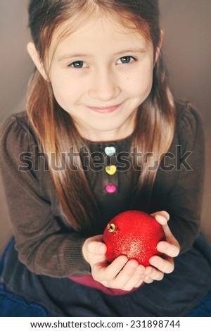 Portrait of cute little girl with a Christmas decoration. At Christmas time. Little girl enjoys Christmas time. - stock photo