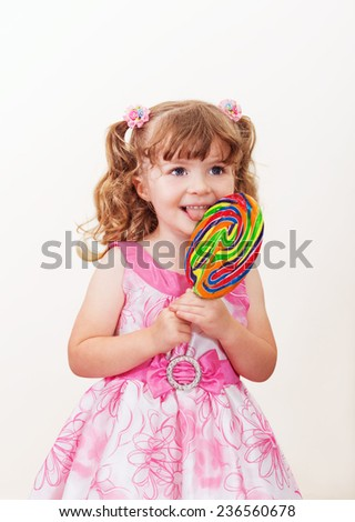 Portrait of cute little girl with big colorful lollipop  on a light background - stock photo