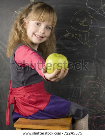 portrait of cute little girl with book and green apple near blackboard - stock photo