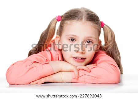 Portrait of cute little girl with head on hands sitting at table isolated over plain background