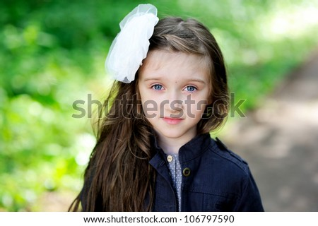 Portrait of cute little girl with white bow in her hair