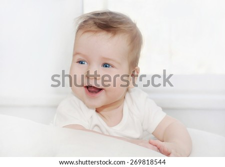 portrait of cute little happy baby boy lying on soft white pillow, happy family concept - stock photo