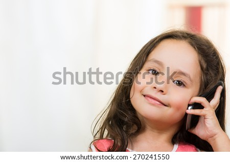 portrait of cute little happy girl using cell phone talking - stock photo
