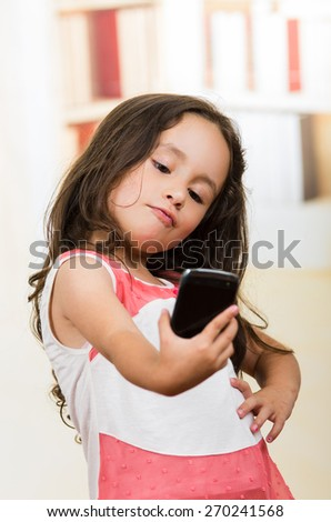 portrait of cute little happy using cell phone taking a selfie - stock photo
