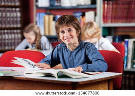 Portrait of cute little schoolboy smiling while sitting with books at table in library - stock photo