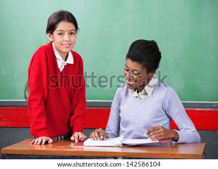 Portrait of cute little schoolgirl with teacher reading binder at desk in classroom - stock photo