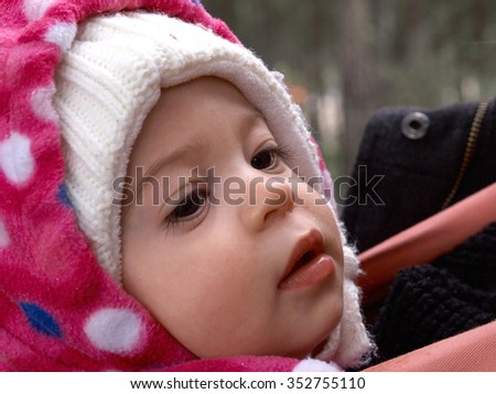 Portrait of cute little toddler baby girl in beautiful warm winter hat        - stock photo