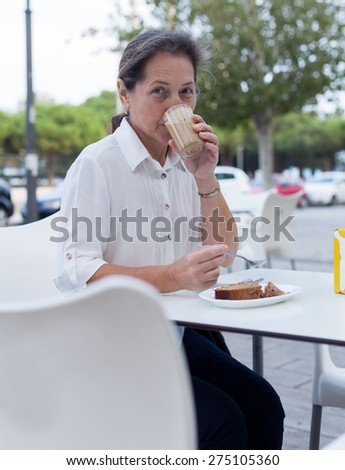 Portrait of  cute mature woman at coffee shop. - stock photo