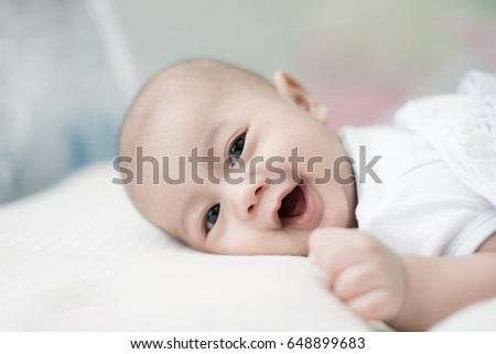 Portrait of cute 3 months Asian baby boy lying down on a blanket and smile