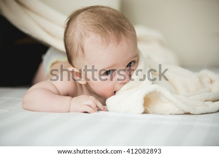 Portrait of cute 6 months baby lying on white sheets