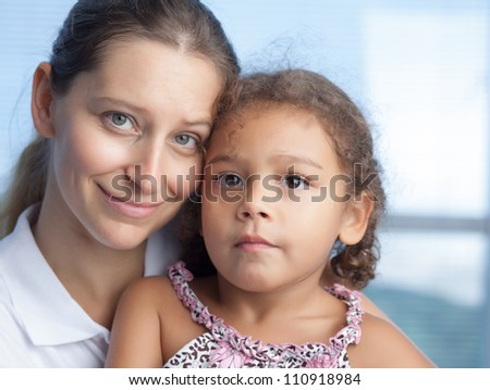 Portrait of cute mother and daughter looking at camera - stock photo