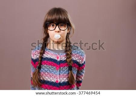 Portrait of cute nerdy little girl blowing bubble gum.Little nerdy girl blowing bubble gum - stock photo