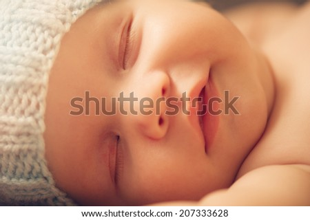 Portrait of cute newborn baby in a funny knitted hat - stock photo