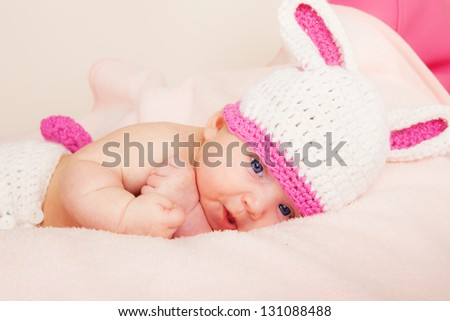 Portrait of cute newborn baby in a funny knitted hat. Childhood or parenting concept.