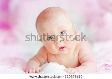 portrait of cute newborn baby on a pink bed
