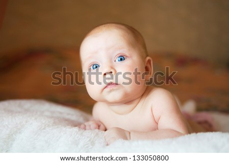 Portrait of cute newborn baby with a funny expression on his face - stock photo