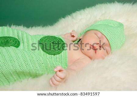 Portrait of cute newborn girl dressed as a green pea - stock photo
