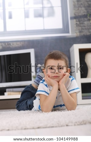 Portrait of cute preschooler boy lying on living room floor, chin in hands, looking at camera. - stock photo