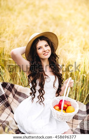 Portrait of cute pretty happy young woman with basket of apples on golden  field, wearing straw hat, harvest season, autumn nature, healthy eating concept
