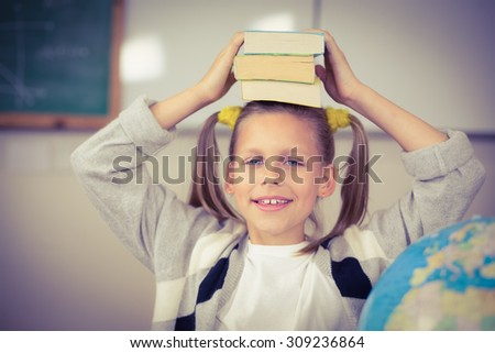 Portrait of cute pupil balancing books on head in a classroom in school - stock photo