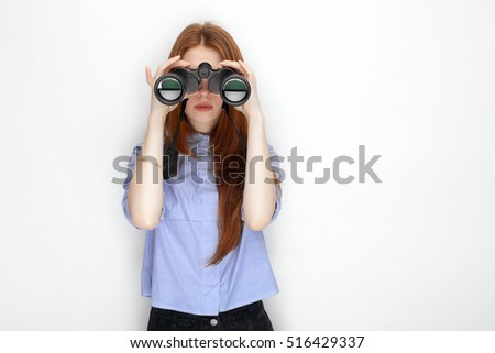 Portrait of cute redhead girl wearing blue striped shirt smiling with happiness and joy looking thru binoculars while posing against white studio background.