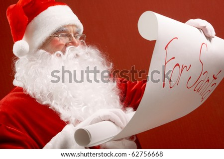 Portrait of cute Santa Claus reading big letter on red background - stock photo