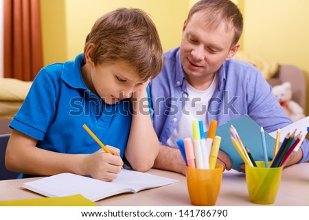Portrait of cute schoolboy and his father making schoolwork at home - stock photo