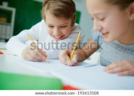 Portrait of cute schoolboy drawing at lesson with his classmate near by - stock photo