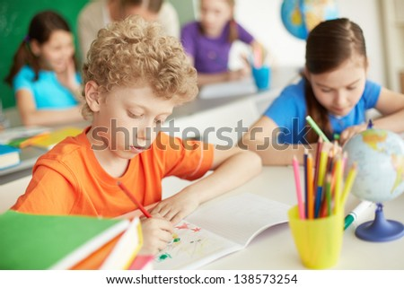 Portrait of cute schoolboy drawing at workplace during lesson - stock photo