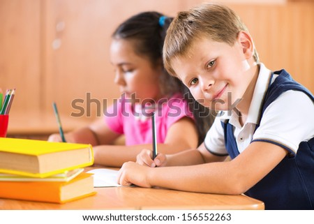 Portrait of cute schoolboy during lesson in classroom at school