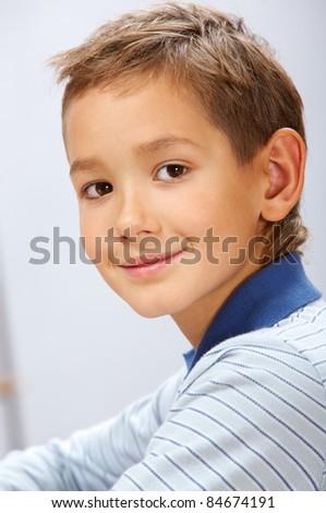 Portrait of cute schoolboy looking at camera - stock photo