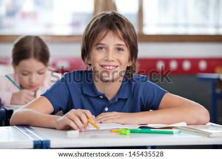 Portrait of cute schoolboy smiling with classmate studying in background at classroom - stock photo