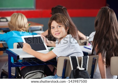 Portrait of cute schoolboy with digital tablet sitting at desk with classmates in classroom - stock photo