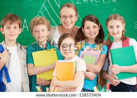 Portrait of cute schoolchildren looking at camera with their teacher among them - stock photo