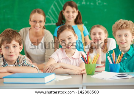 Portrait of cute schoolchildren looking at camera with their teacher and classmates on background - stock photo